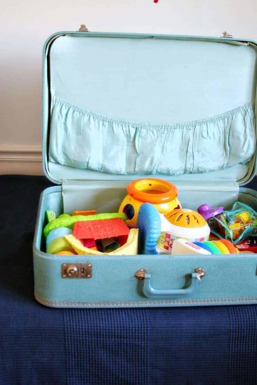 Blue vintage suitcase used as toy storage