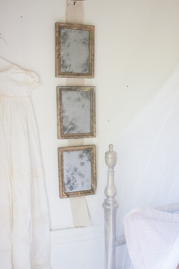 3 gold frames turned into antique looking mirrors hanging in a row in the wall with a white walls. Corner of bed frame is shown in the corner