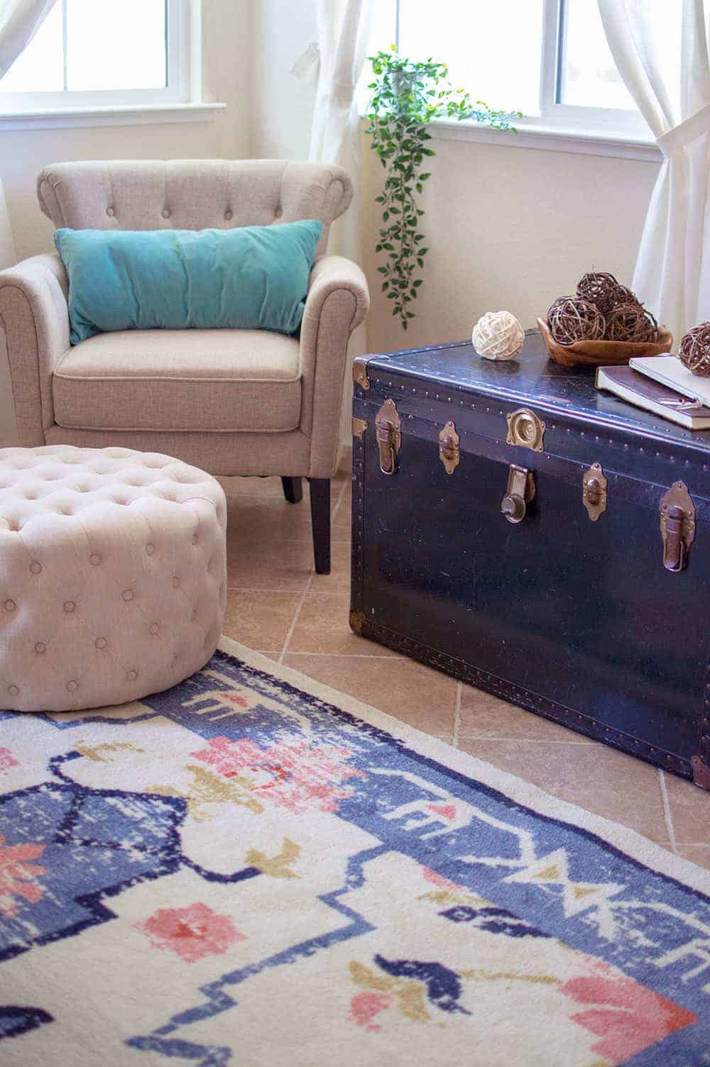 Corner of living room with vintage trunk used as side table, cream colored furniture, teal throw pillow and colorful vintage inspired rug