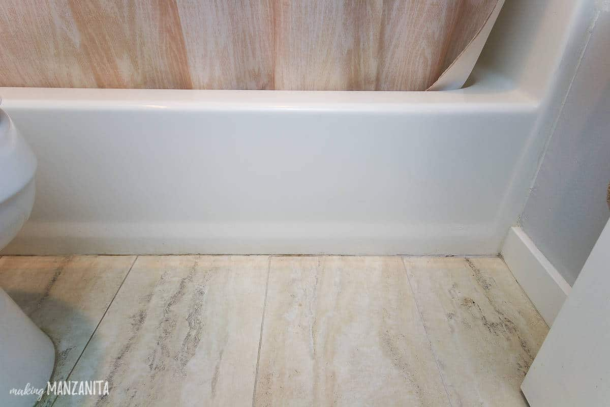 Caulk line at the base of a bath tub where the flooring meets the tub that dirty and cracked and needs replacing