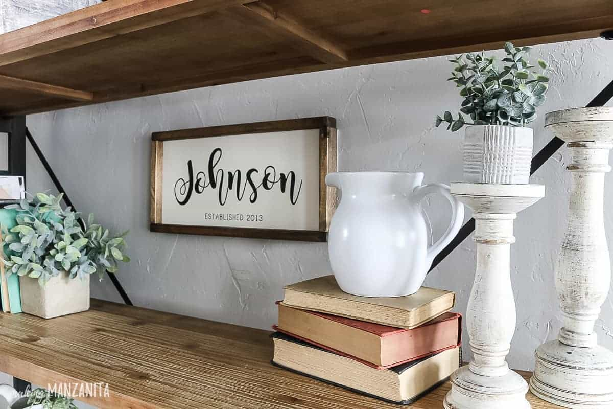 Farmhouse shelf decorations with faux greenery, vintage books, candlesticks, white farmhouse pitcher and family name sign hanging on wall