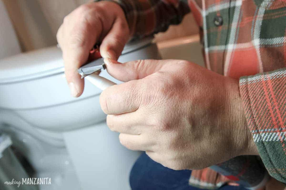 Man hands holding a tub of caulk and opening the tip with a utility knife held at a 45 degree angle