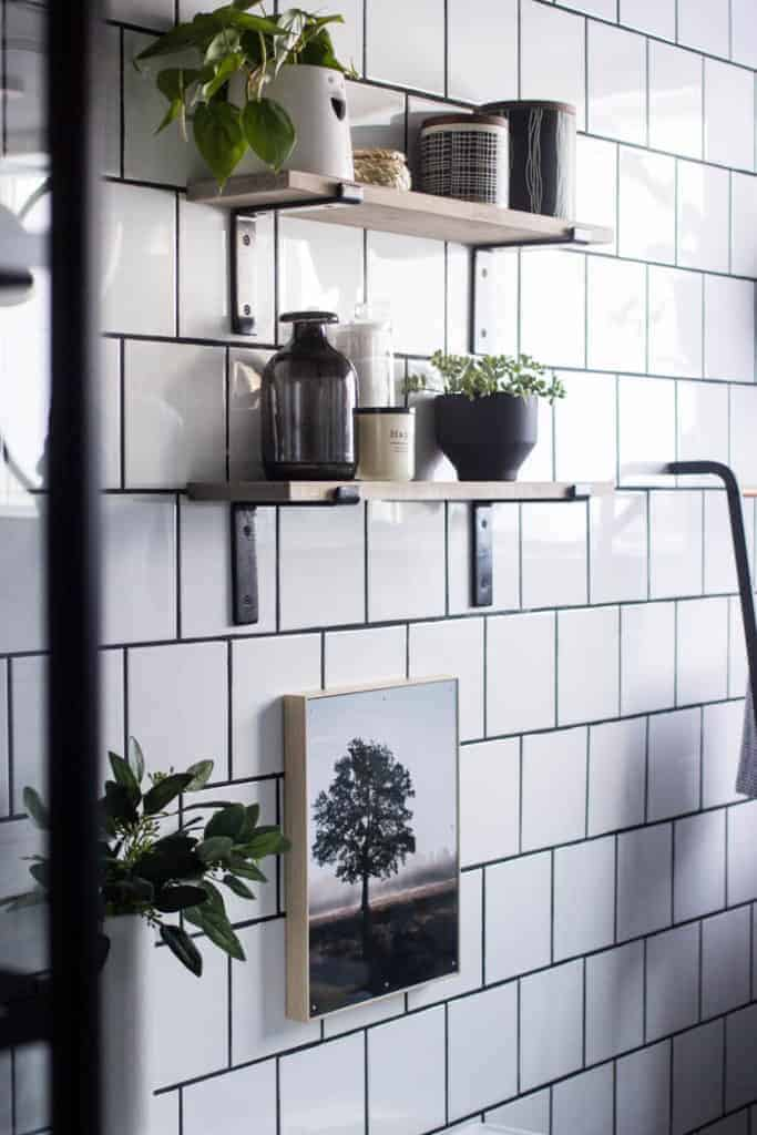 White square tile wall with dark grout and two floating shelves with black brackets drilled into tile with various vases and plants as decor