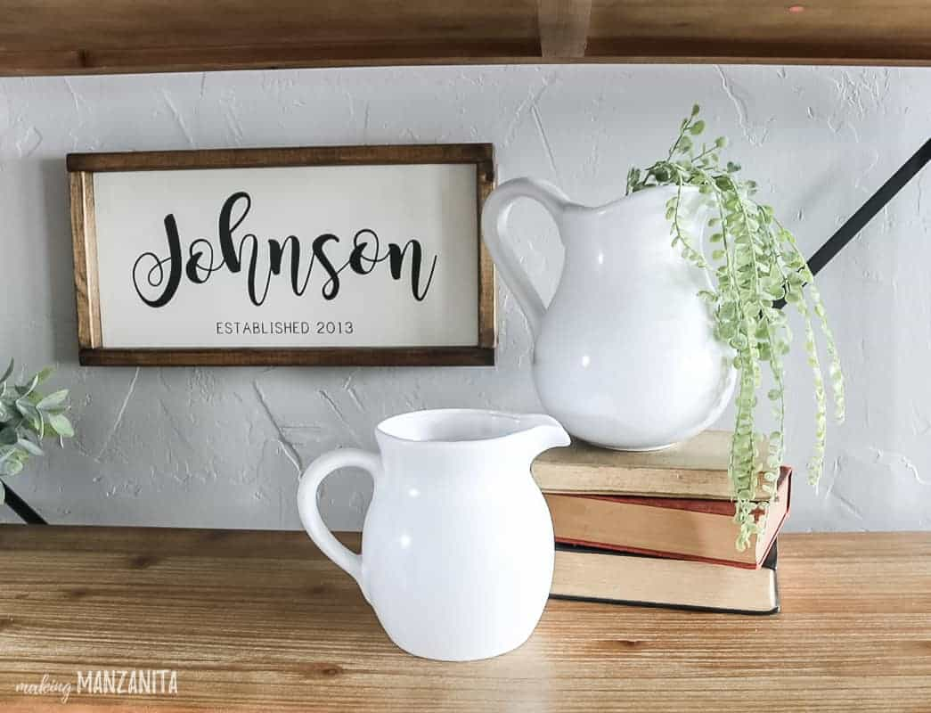 Shelf decor idea with a farmhouse sign hanging on the wall in the background that says Johnson and 2 white farmhouse pitchers displayed with a stack of vintage books and faux greenery