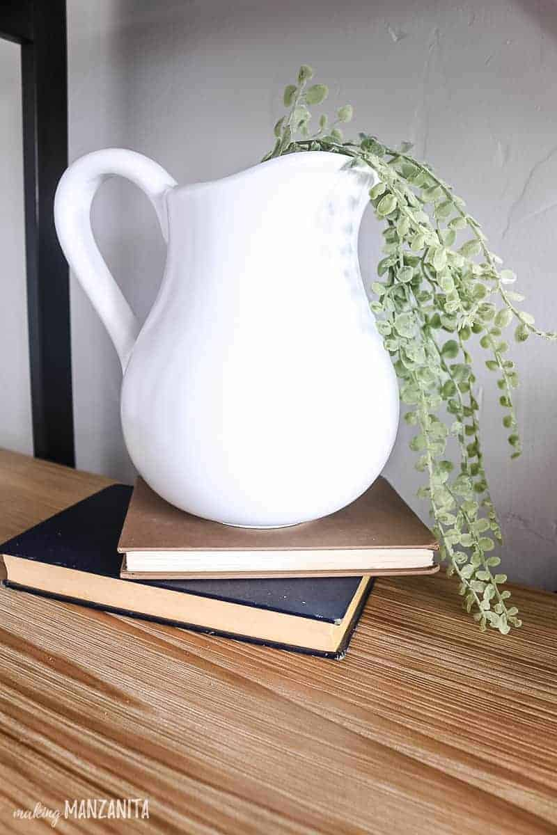 Vintage books on a wood shelf topped with a white pitcher with faux greenery flowing out of it