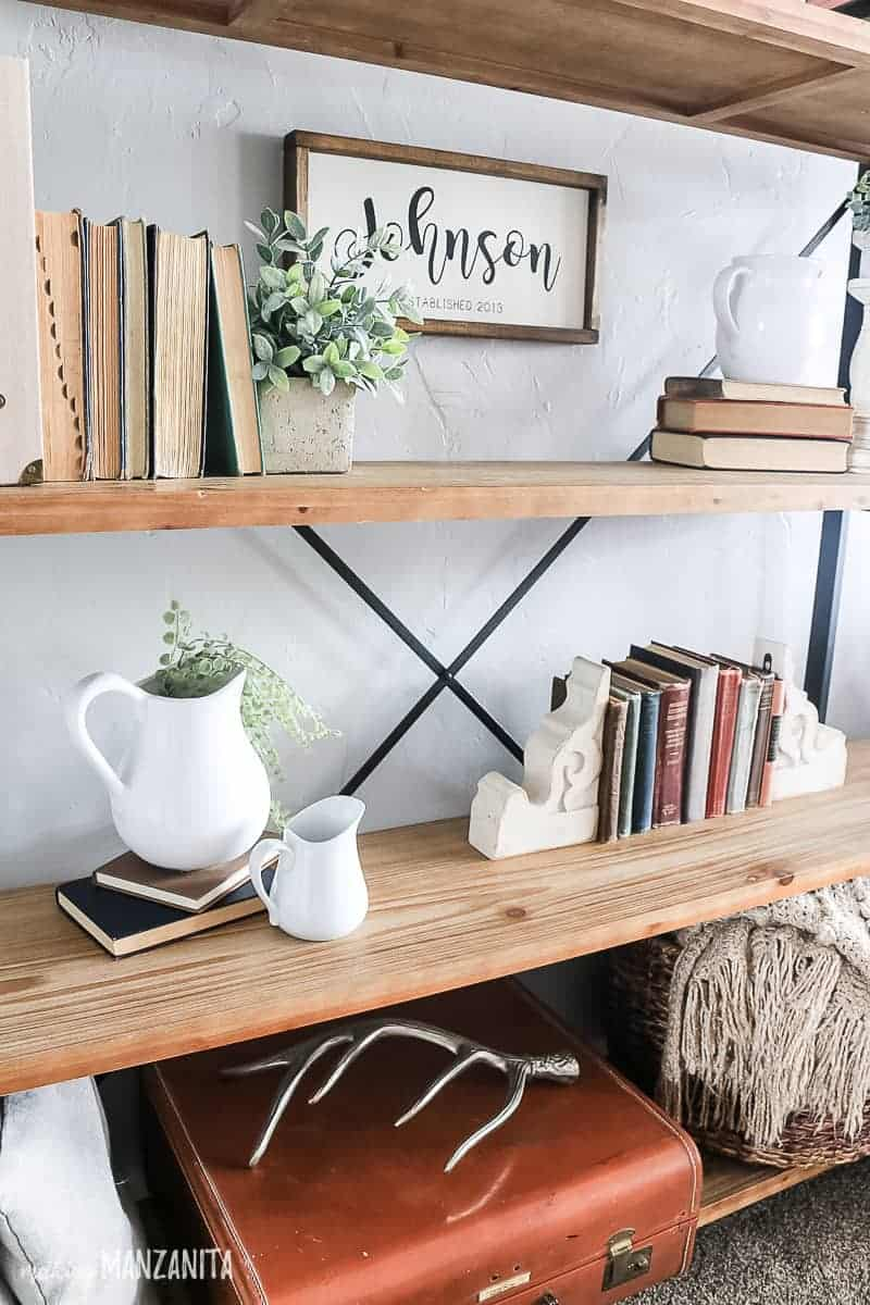 Vintage decor displayed on a shelving unit with farmhouse style showing white farmhouse jugs, vintage books, corbles, greenery and faux plants, farmhouse sign, vintage suite case and silver antler