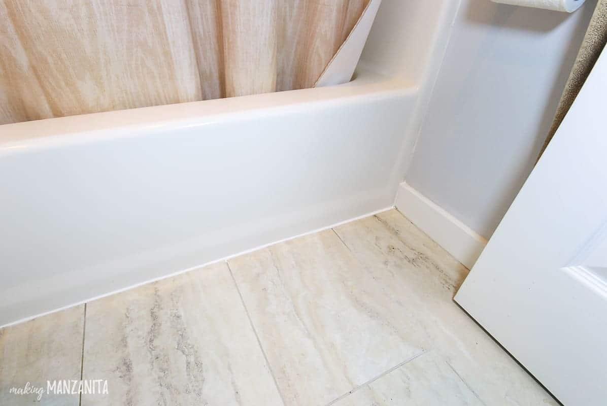 A newly recaulked tile line on the bathroom floor.