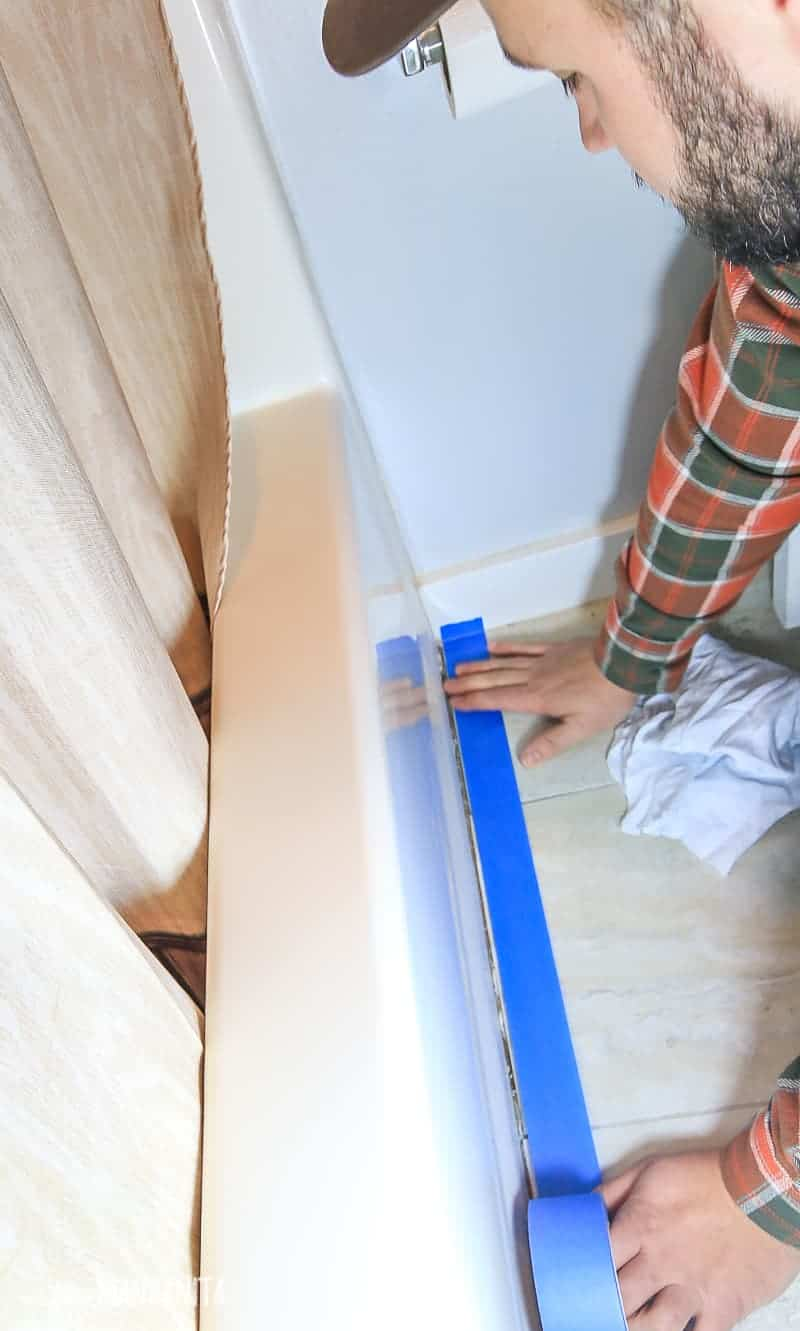 Man in bathroom adding a line of painter's tape in front of bathtub before recaulking the area where the tub meets the flooring
