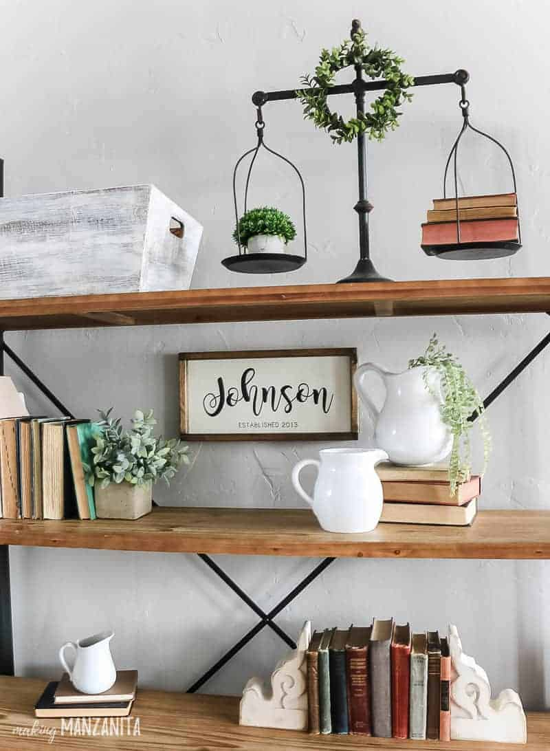 Farmhouses shelving unit with vintage inspired decor showing metal scale, vintage books, white farmhouse pitchers with gray walls in the background