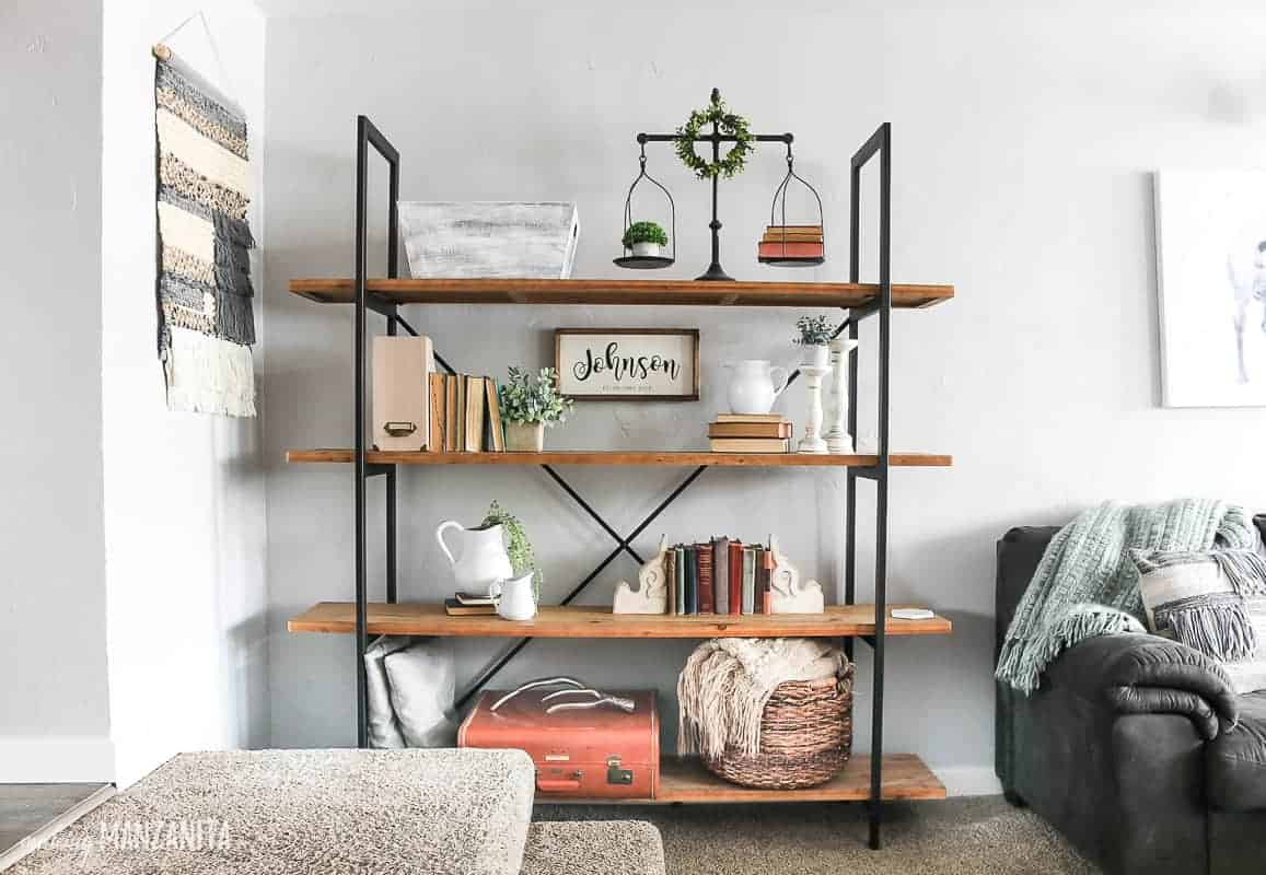 Modern farmhouse shelving unit in a living room with light gray walls and filled with farmhouse style decor of vintage books, faux greenery, white pitchers, and other vintage finds.