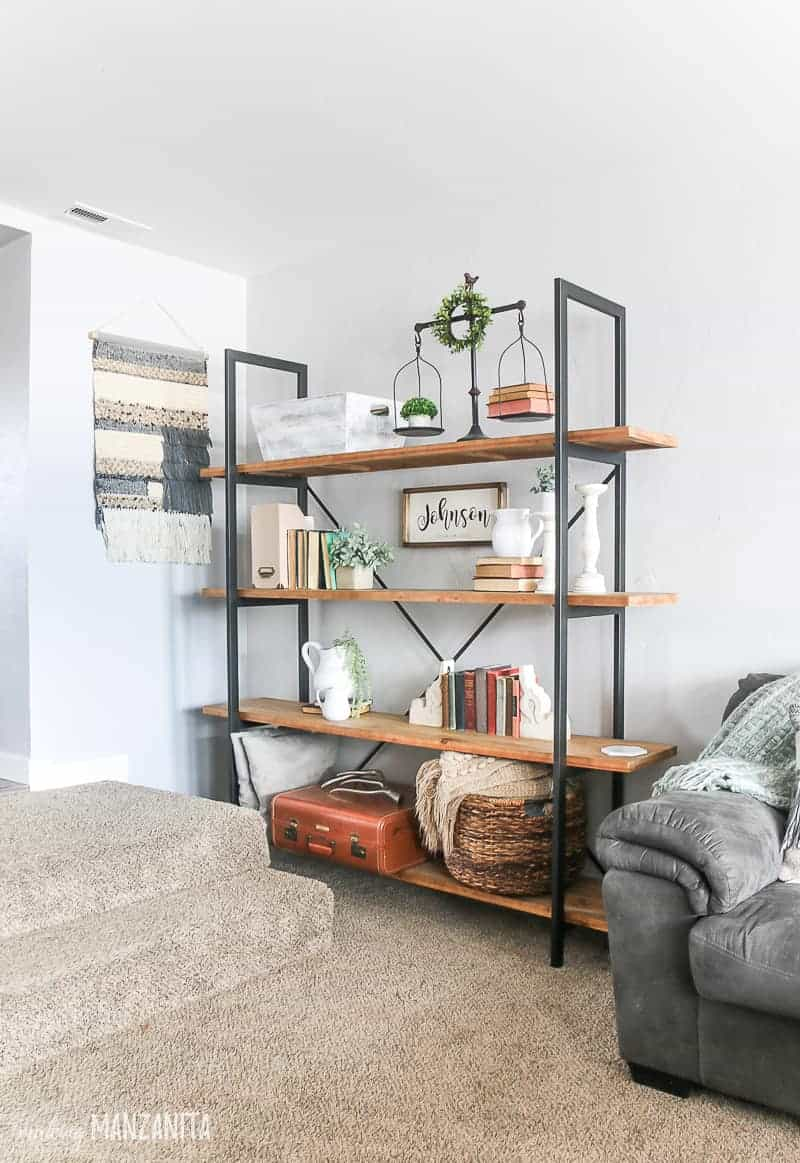 Corner of living room with large bookcase with rustic wood shelves, metal brackets, farmhouse decor on shelves, light gray paint on walls and woven wall hanging