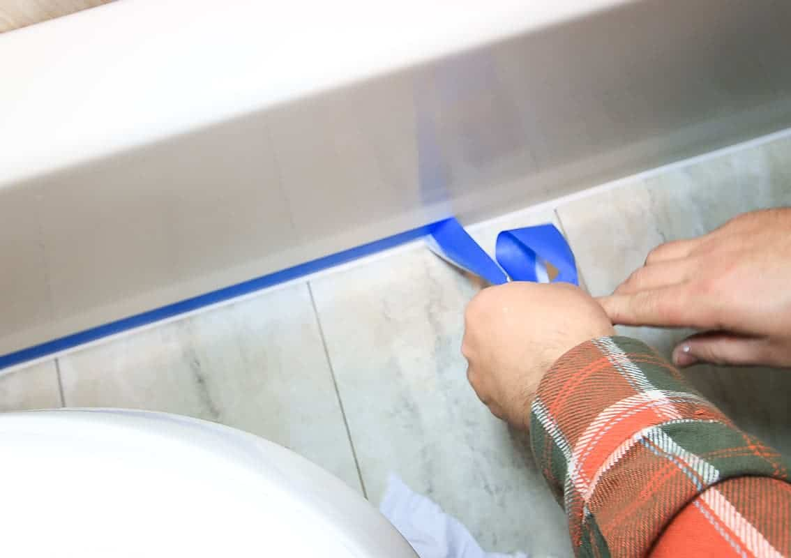 Man's hands removing painter's tape from bathroom after applying new white caulk at the base of the bath tub