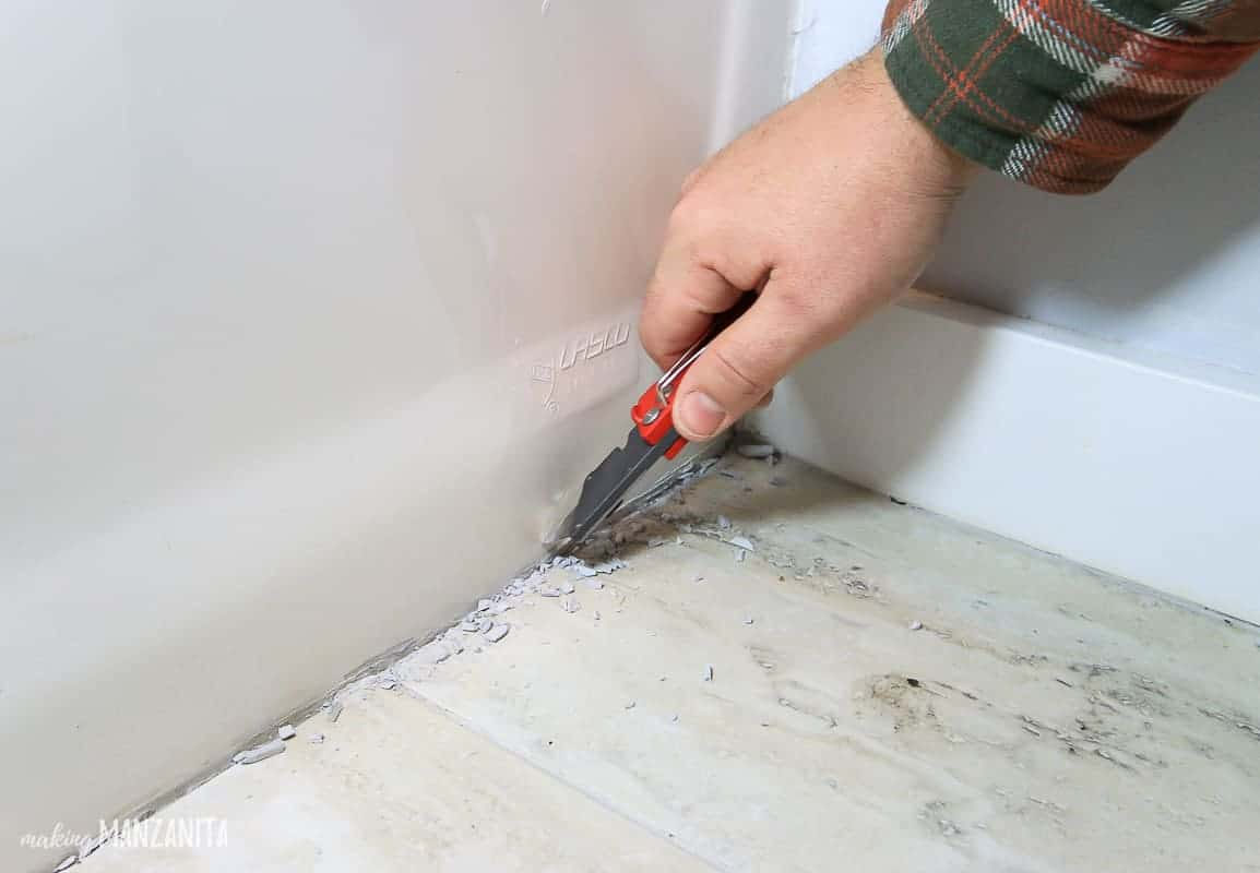 Removing old caulk in bathroom with a razor blade before recaulking