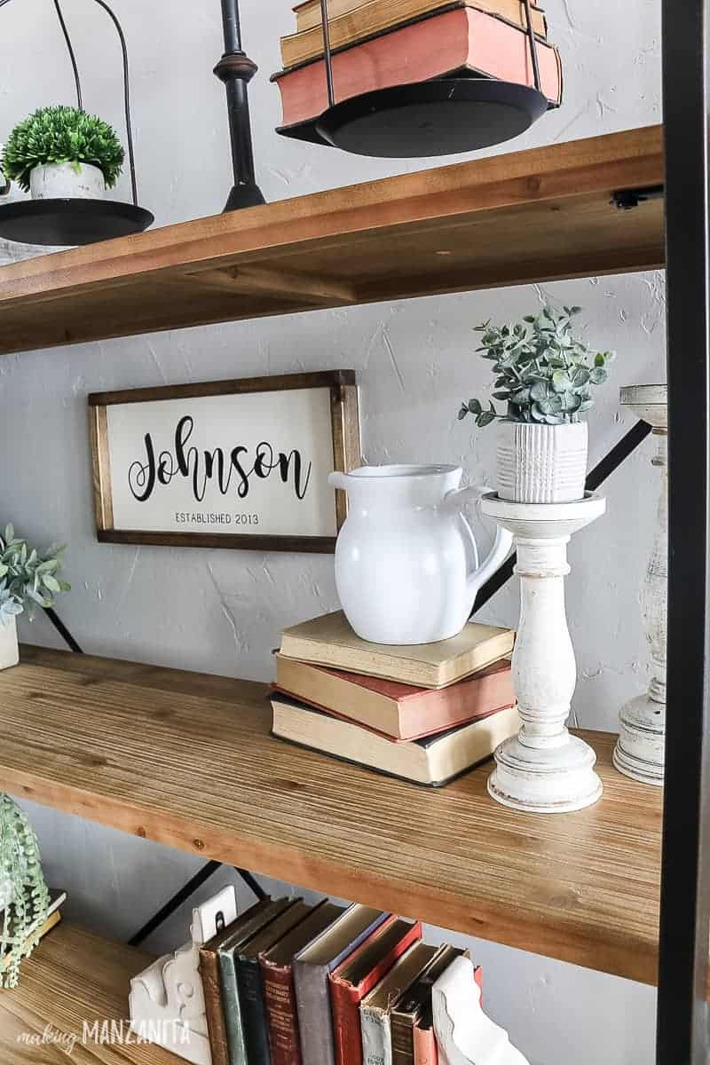 Decorating shelf ideas with farmhouse style decorations on a modern farmhouse shelving unit with antique books, candelstick holders, and metal scale