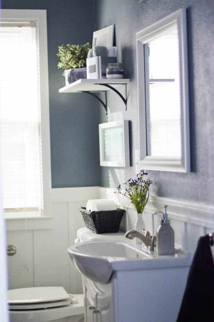 Blue walls in bathroom with white board and batten on the bottom, white shelf hanging above toilet, mirror with white frame