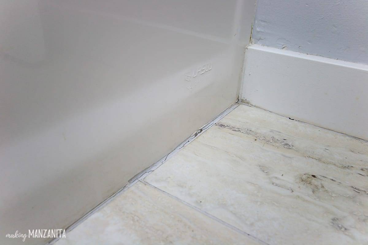 Close up shot of a caulk line at the base of a bath tub where the flooring meets the tub that dirty and cracked and needs replacing