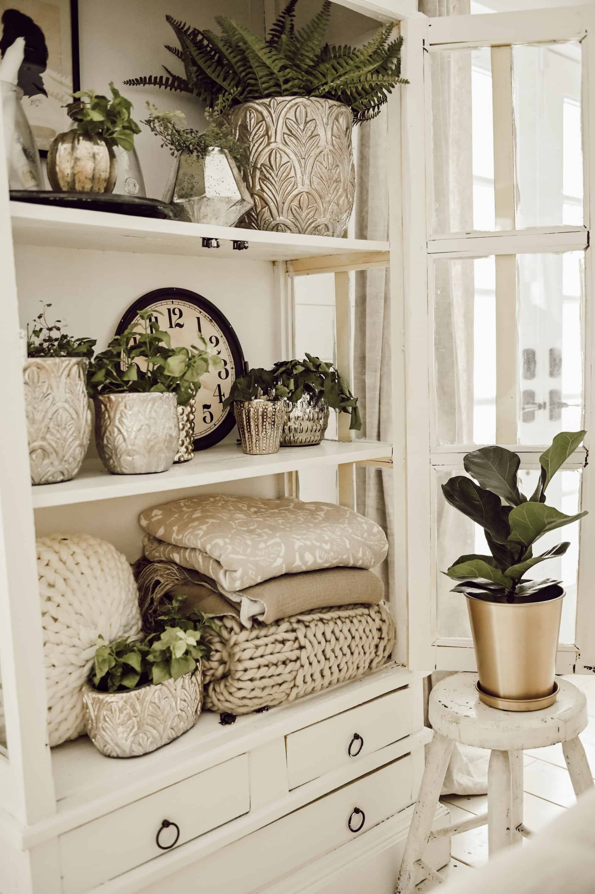 White vintage cabinet with doors open showing farmhouse styled decor like plants, folded cozy planets, clock