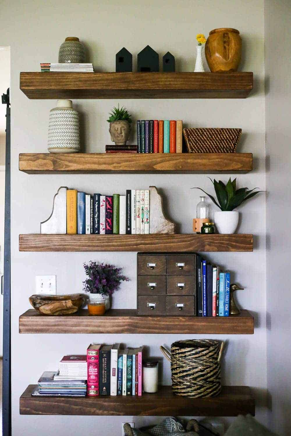 Chunky wood floating shelves in living room decorated with plants, vases, colorful books and baskets