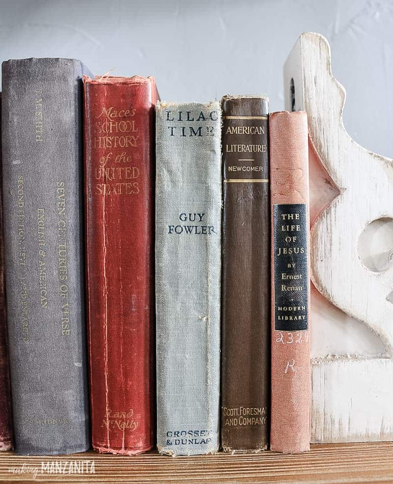 Vintage books on a shelf with worn covers and vintage corbel used as a bookend