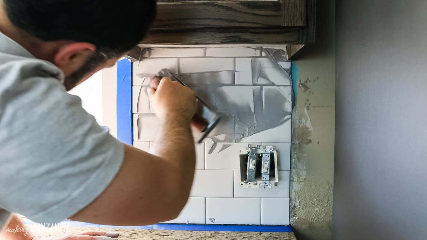 Man applying gray grout with a rubber grout float over white subway tile backsplash in kitchen under upper cabinets