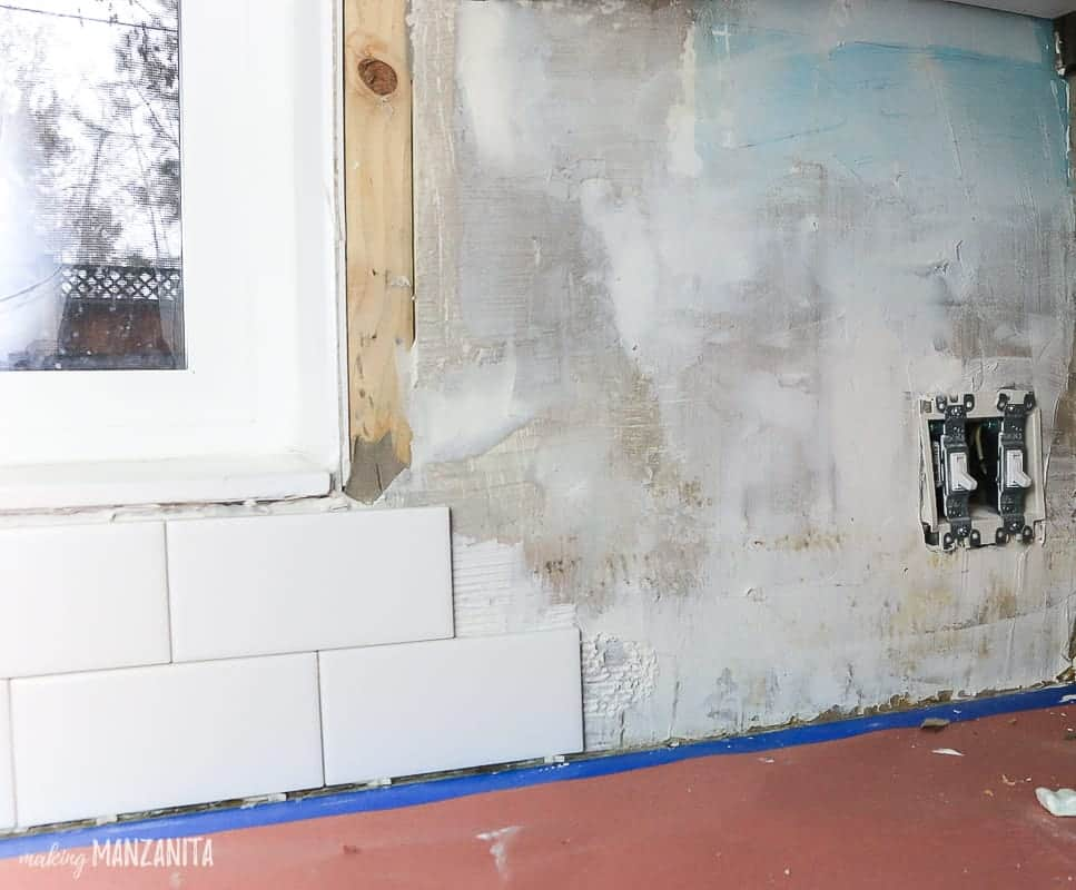 Process photo of subway tile getting installed in a kitchen with tile adhesive