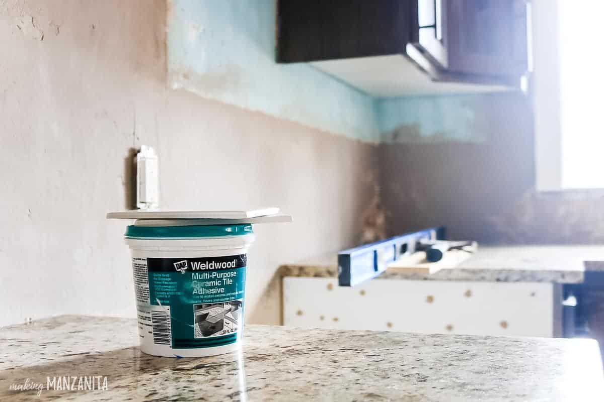 Close up image of a jar of DAP Weldwood multi-purpose ceramic tile adhesive sitting on a countertop in front of blank wall where a kitchen tile backsplash will go