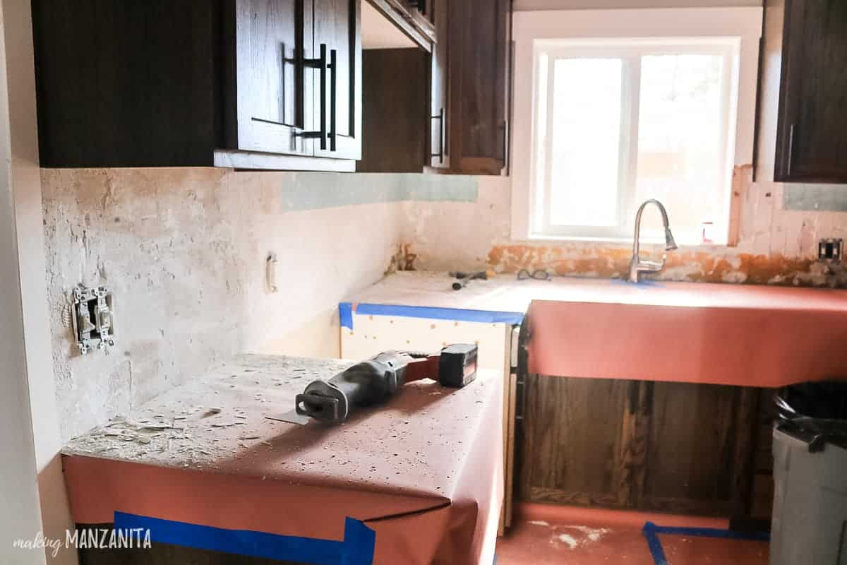 Mess in kitchen after tile removal demo with counter tops covered with red rosin heavyweight paper