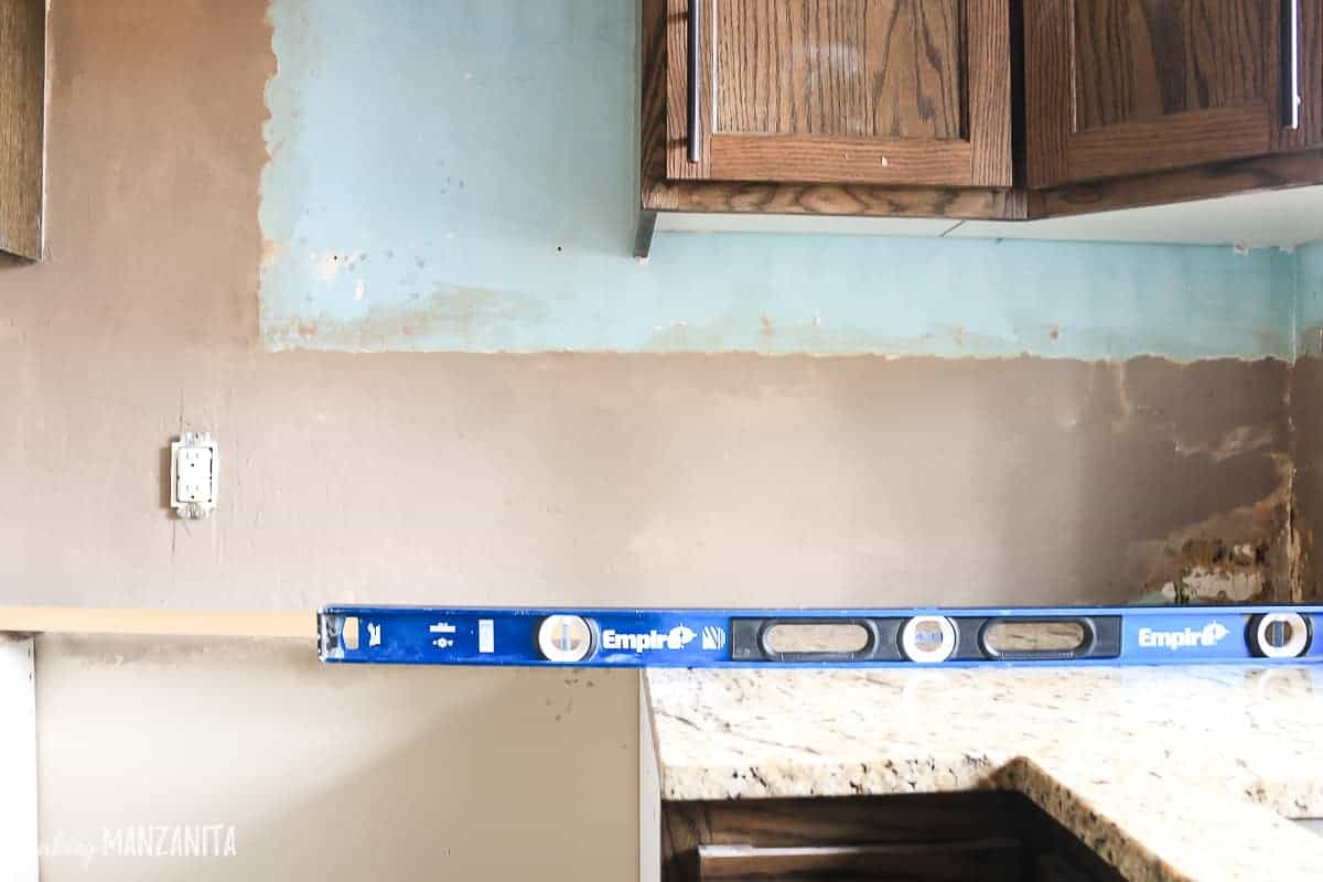 Large blue level sitting on top of a kitchen countertop in kitchen where the backsplash area is bare with concrete patch and ready for subway tile backsplash to be installed