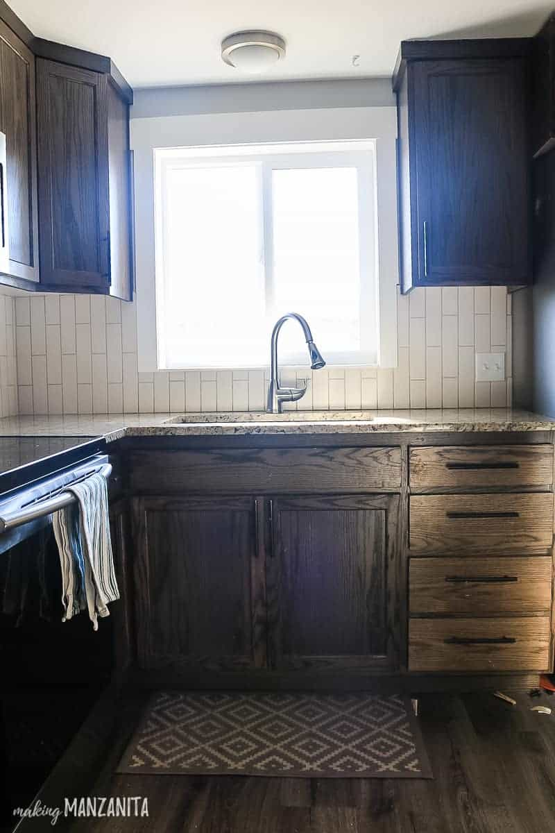 Kitchen with dark wood cabinets, kitchen sink with window above it and tan tile backplash