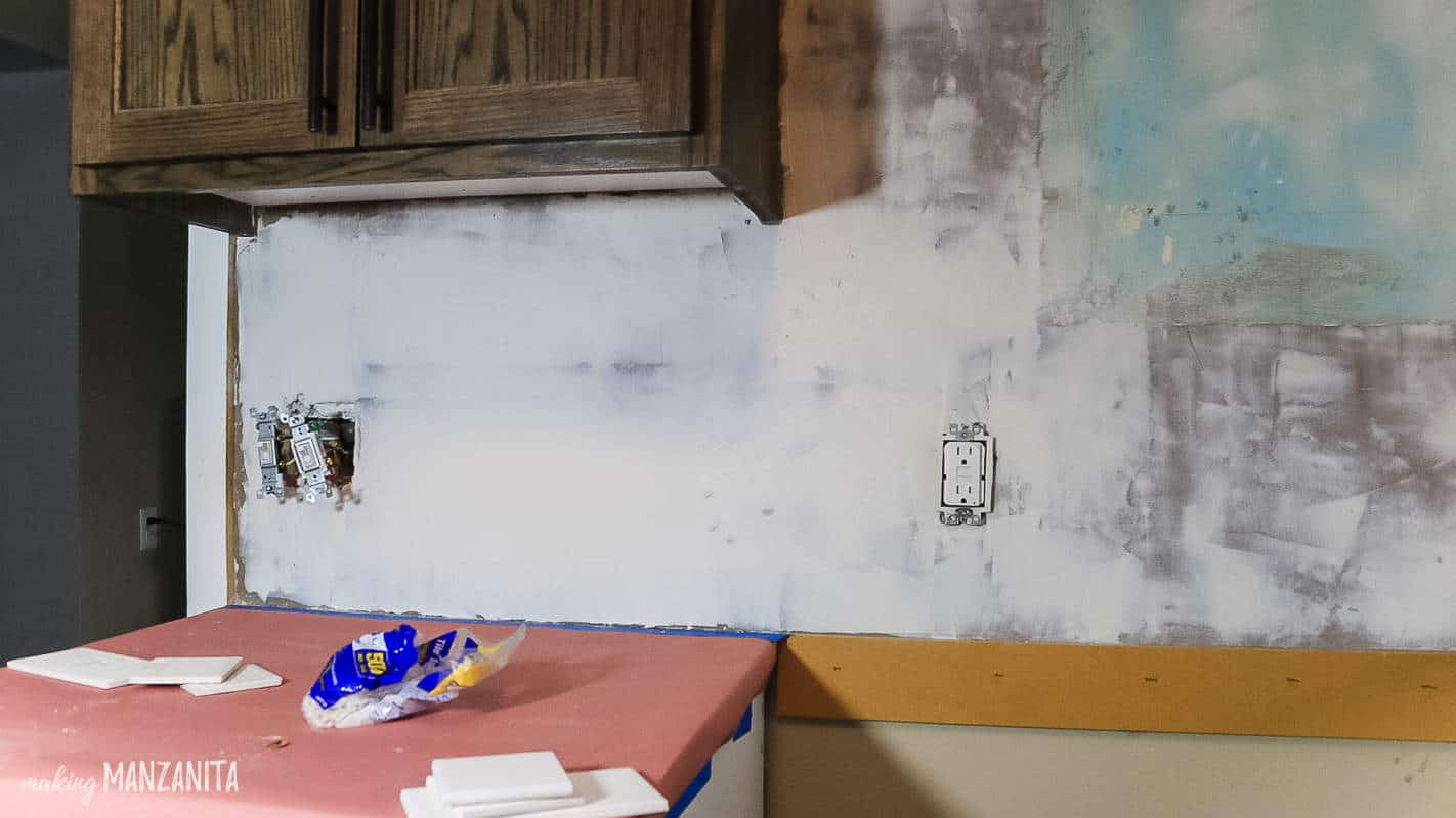 Thin skim coat of tile adhesive applied to wall before starting to install tile backsplash