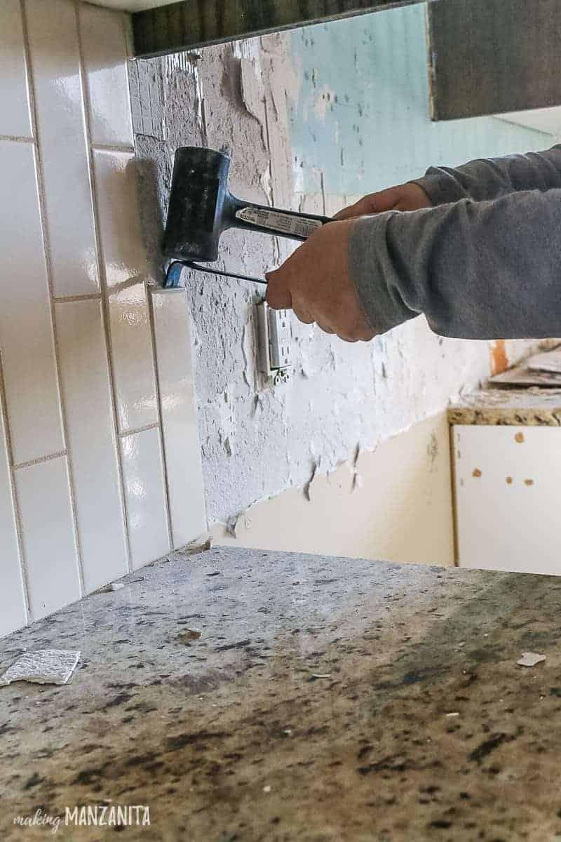 Removing tile on kitchen backsplash with crow bar and hammer