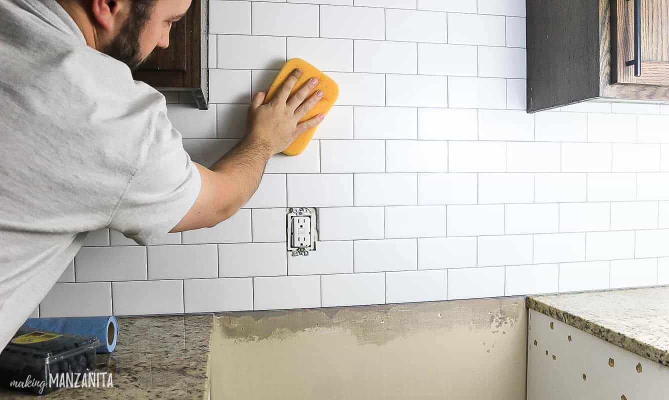 Removing grout haze on white subway tile with a mixture of vinegar and water with a wet yellow sponge