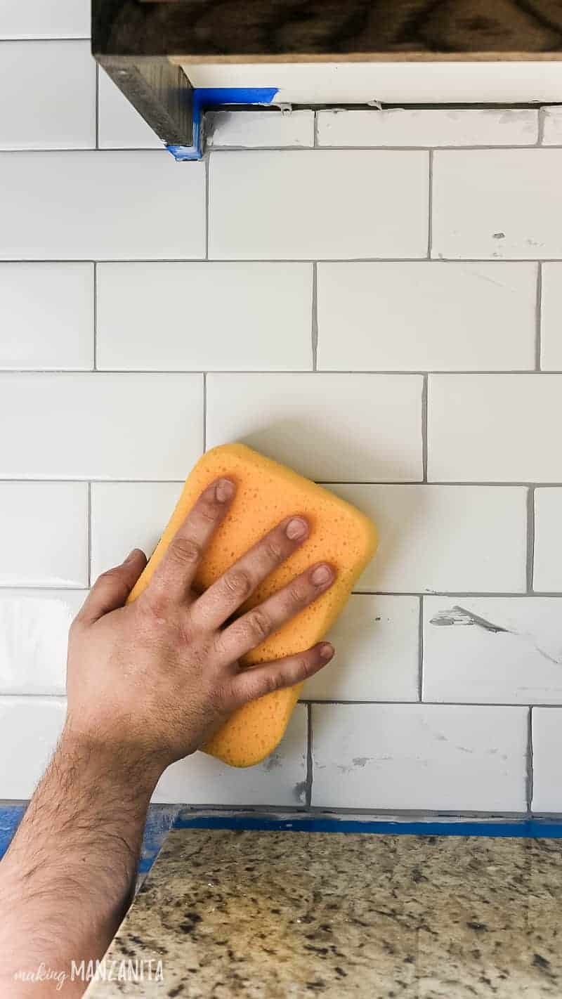 Wiping off excess gray grout on white subway tile backsplash in kitchen with a wet yellow sponge