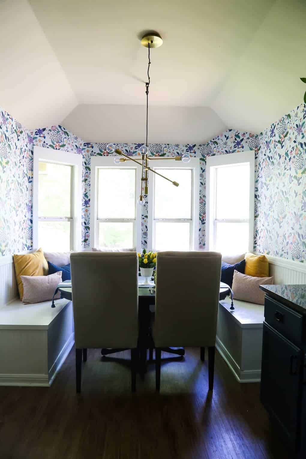 After picture with light and bright dining room with floral wallpaper, built in bench seating, modern gold light and throw pillows