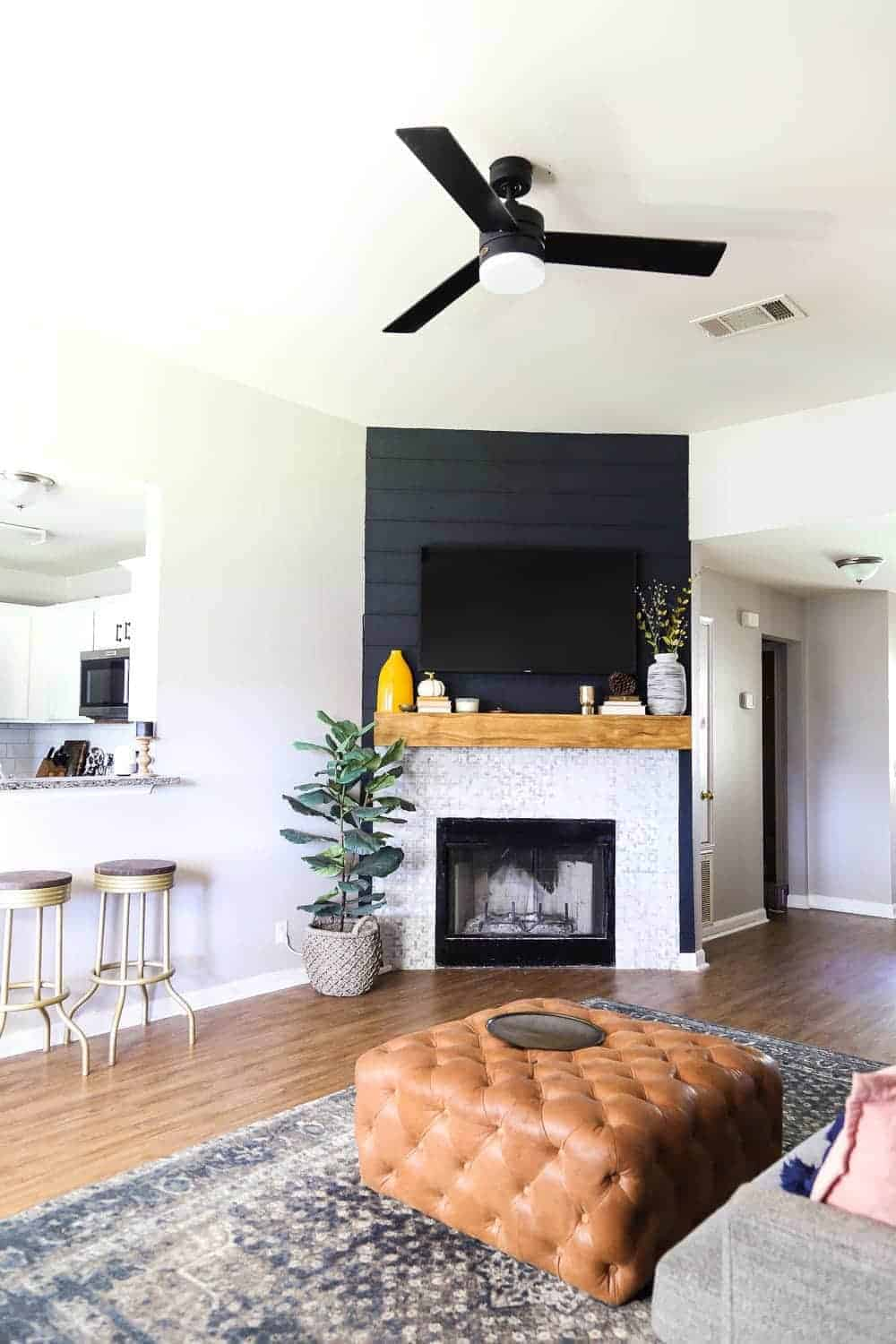 Light and bright living room with contemporary style, black shiplap fireplace, black modern ceiling fan, leather tufted ottoman