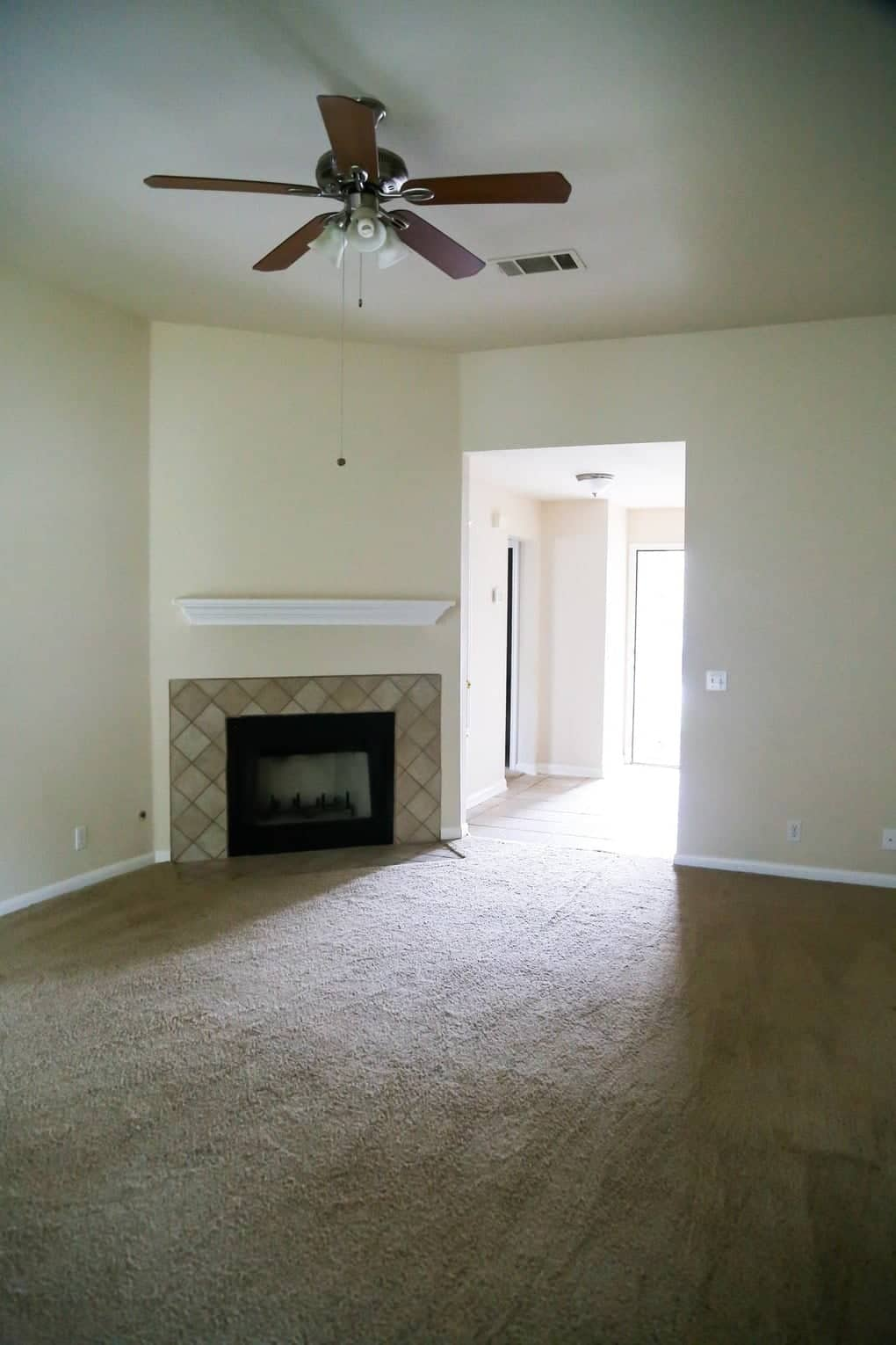 Old and dark living room with outdated tan walls, tan carpet and no furniture