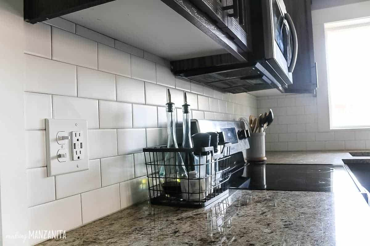 Matte finish 3x6 white subway tile backsplash with thin grout lines and a light gray grout installed in a modern farmhouse kitchen with upper and lower dark wood cabinets and stainless steel appliances