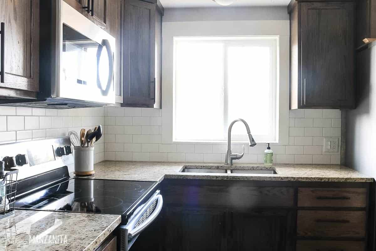 Modern farmhouse style kitchen with new subway tile backsplash, wooden cabinets, window over sink and tan granite countertops