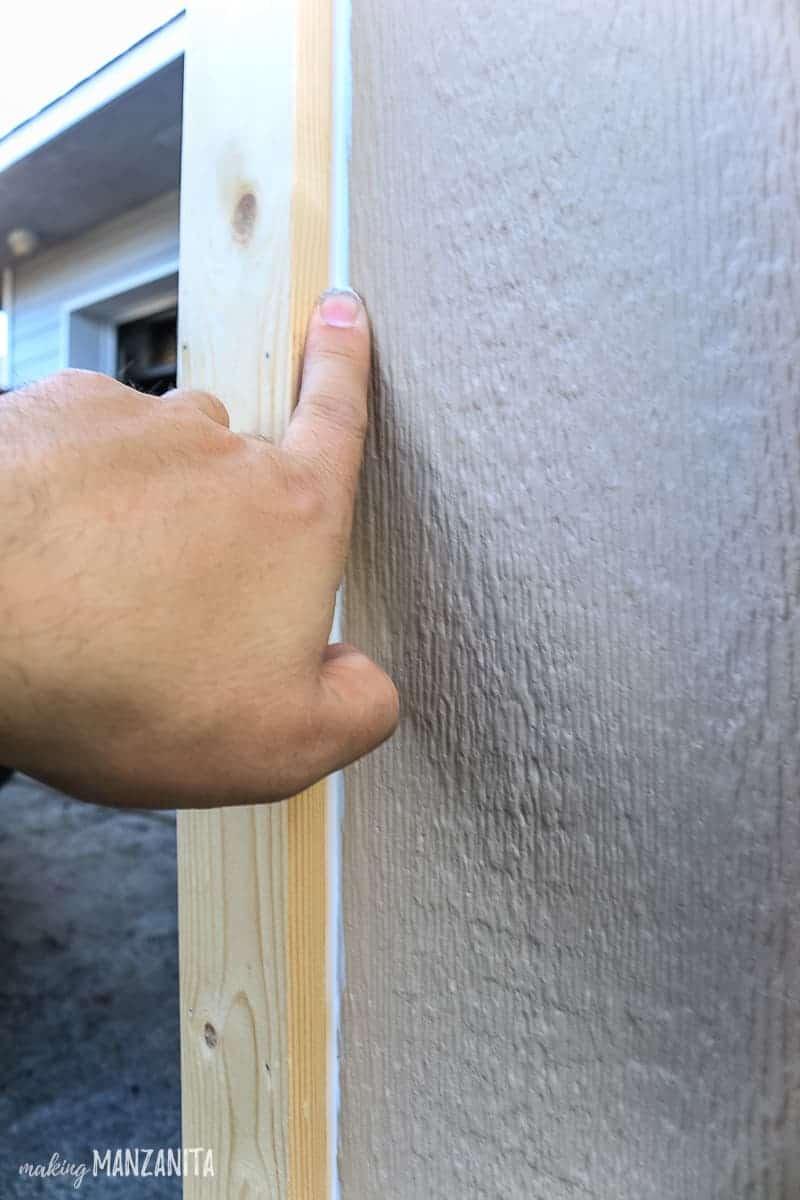 Man tooling bead of caulk on exterior porch post trim