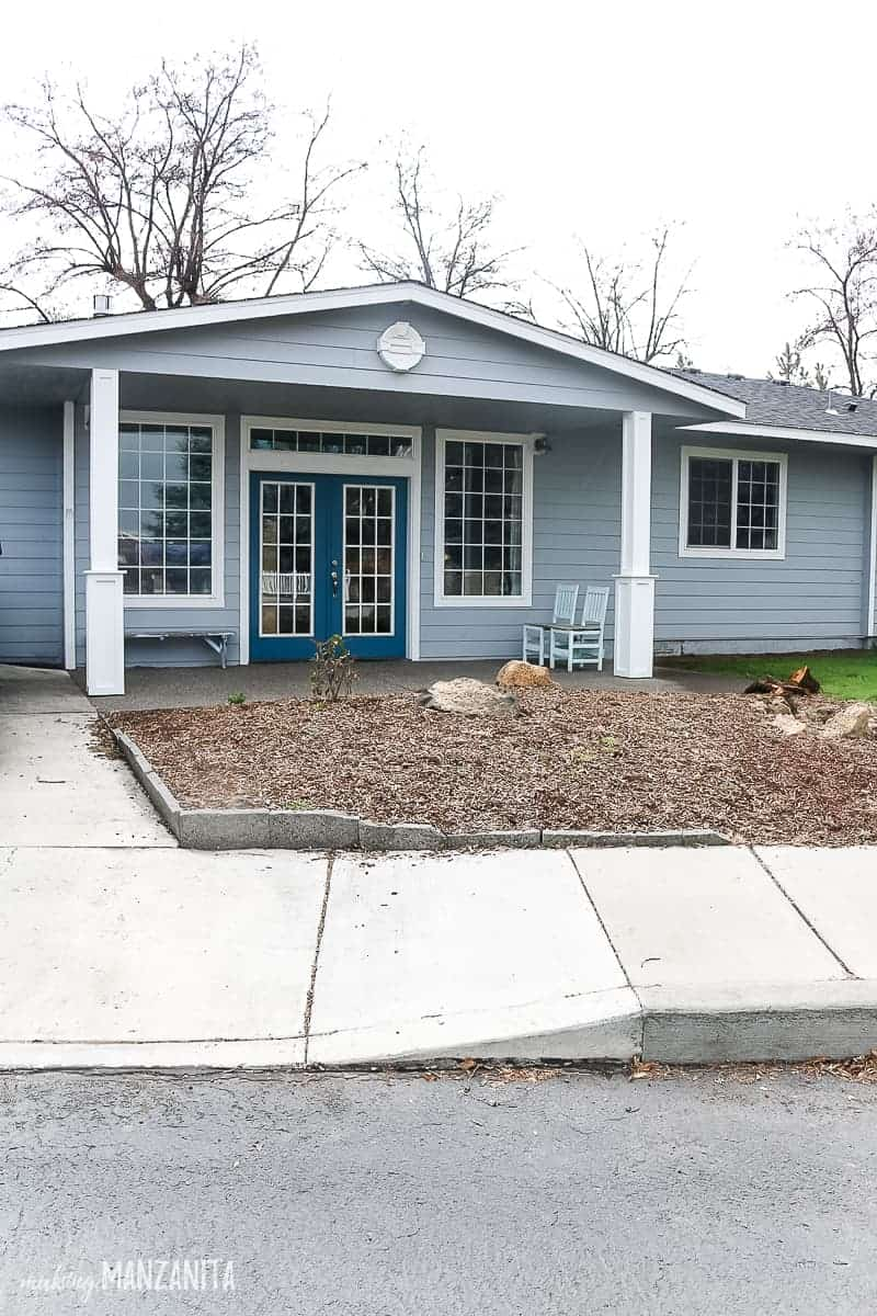 Front exterior of a ranch style house with front porch posts that are trimmed out with a farmhouse style and painted white. House is a light blue color
