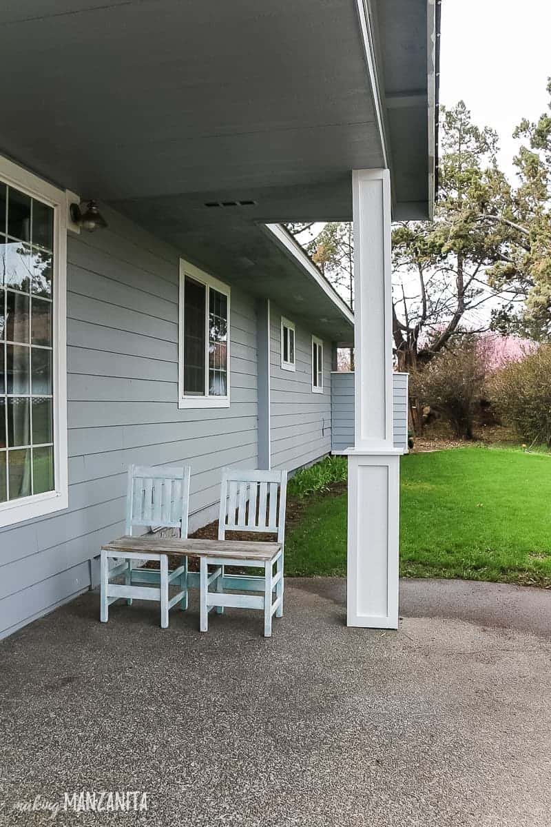 Side view of front yard and patio with new DIY porch posts with craftsman style trim added and an upcycled chair bench sitting on porch area with grass shown in background