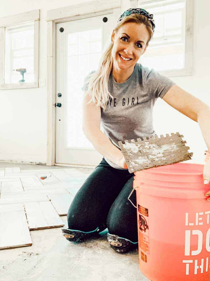 Woman sitting on floor tiling floor smiling at camera while holding a trowel next to a bucket
