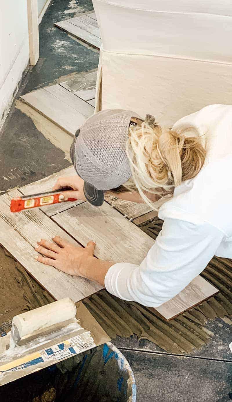 Woman installing herringbone pattern tile flooring holding a level and wearing a baseball cap
