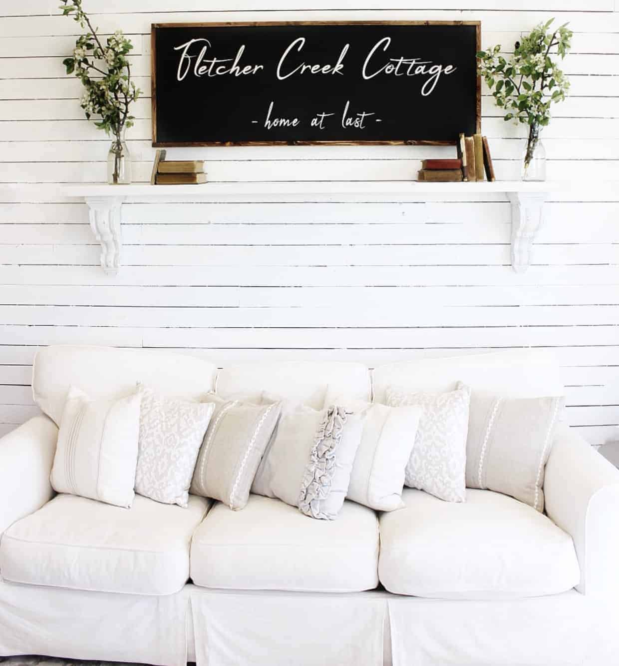 Farmhouse style living room with white couch and neutral throw pillows with white skinny shiplap walls, a shelf above the couch with a farmhouse style sign that says Fletcher Creek Cottage home at last and vintage books and greenery