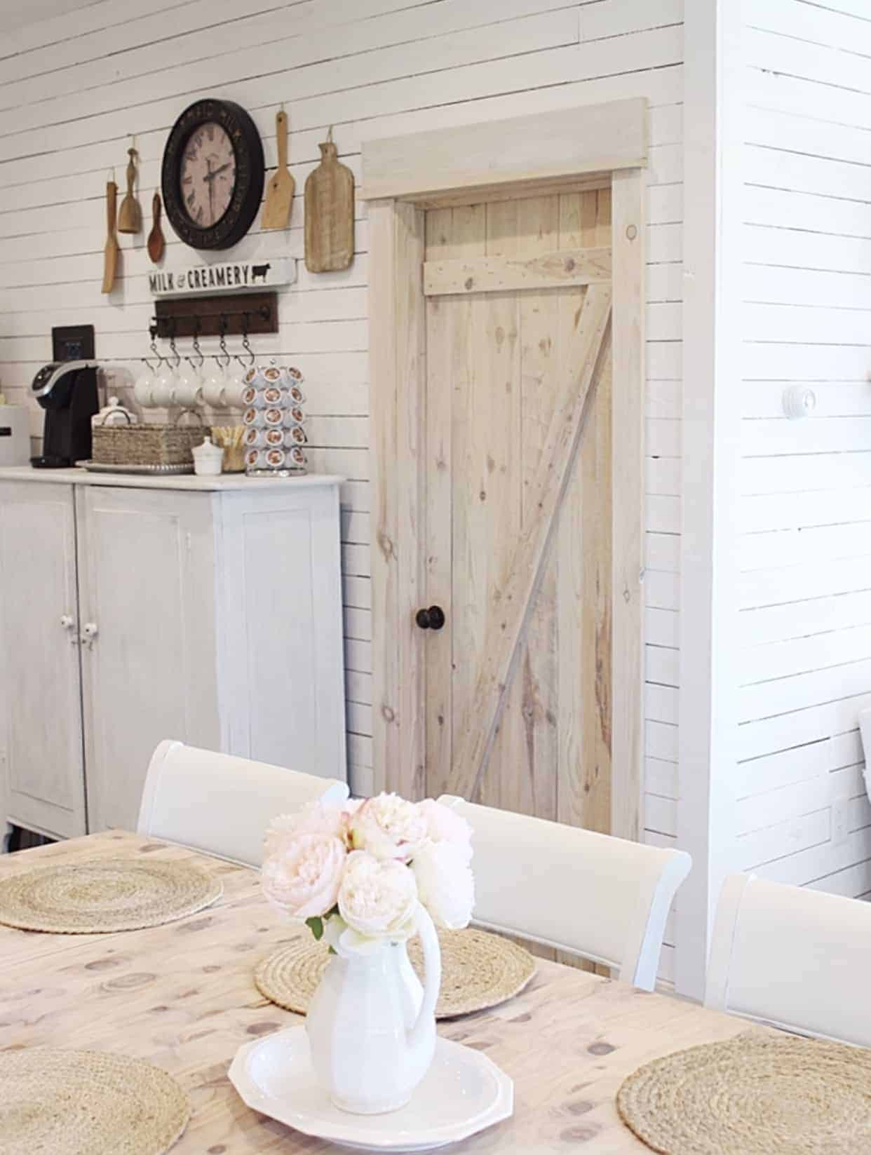 White shiplap walls with light wood door that was barn door style, cutting boards hung for wall decor above a kitchen cabinet used as a coffee bar and a corner of the dining room table shown in the foreground