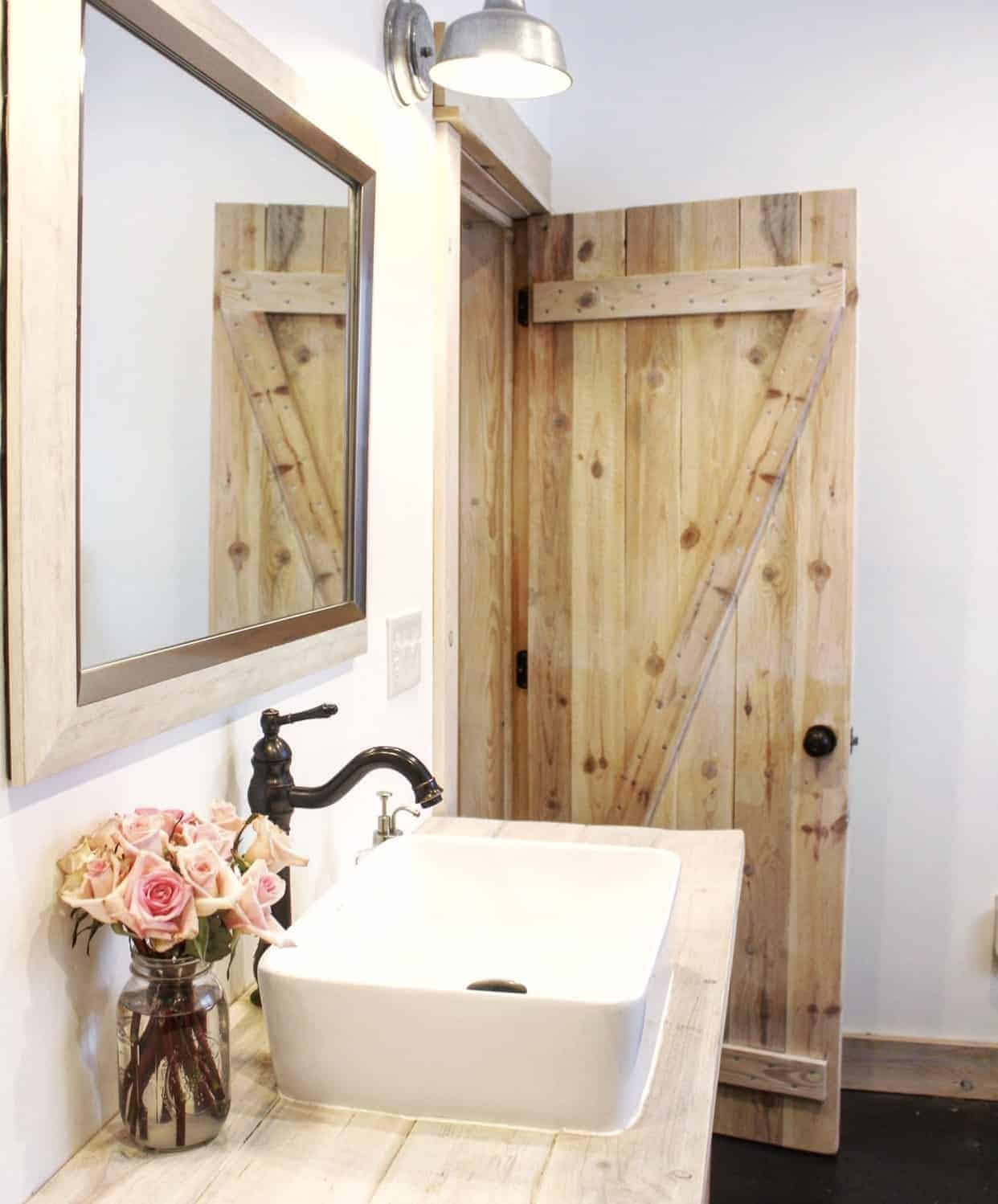 Farmhouse style bathroom with a wooden barn door, pendant barn style lighting, large farmhouse basin sink above wooden countertops with a vase of pink roses on the counter