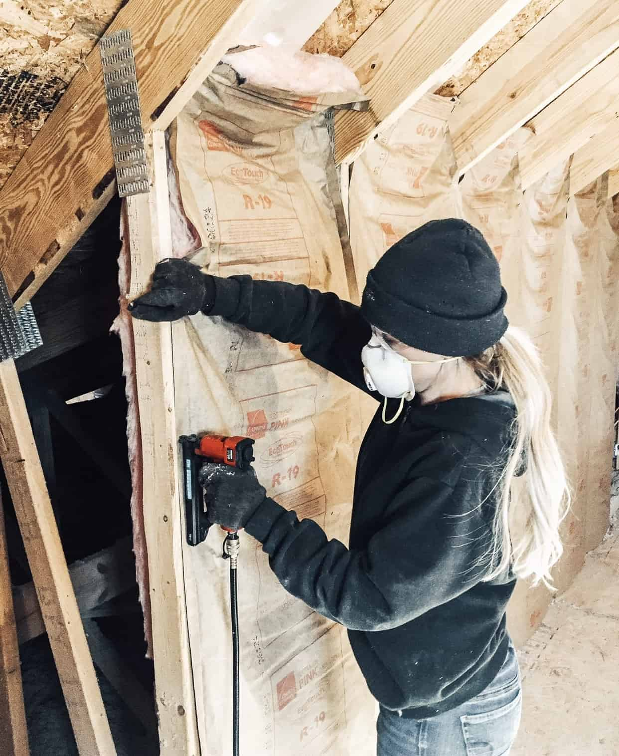 Woman installing insulation in loft area with open walls