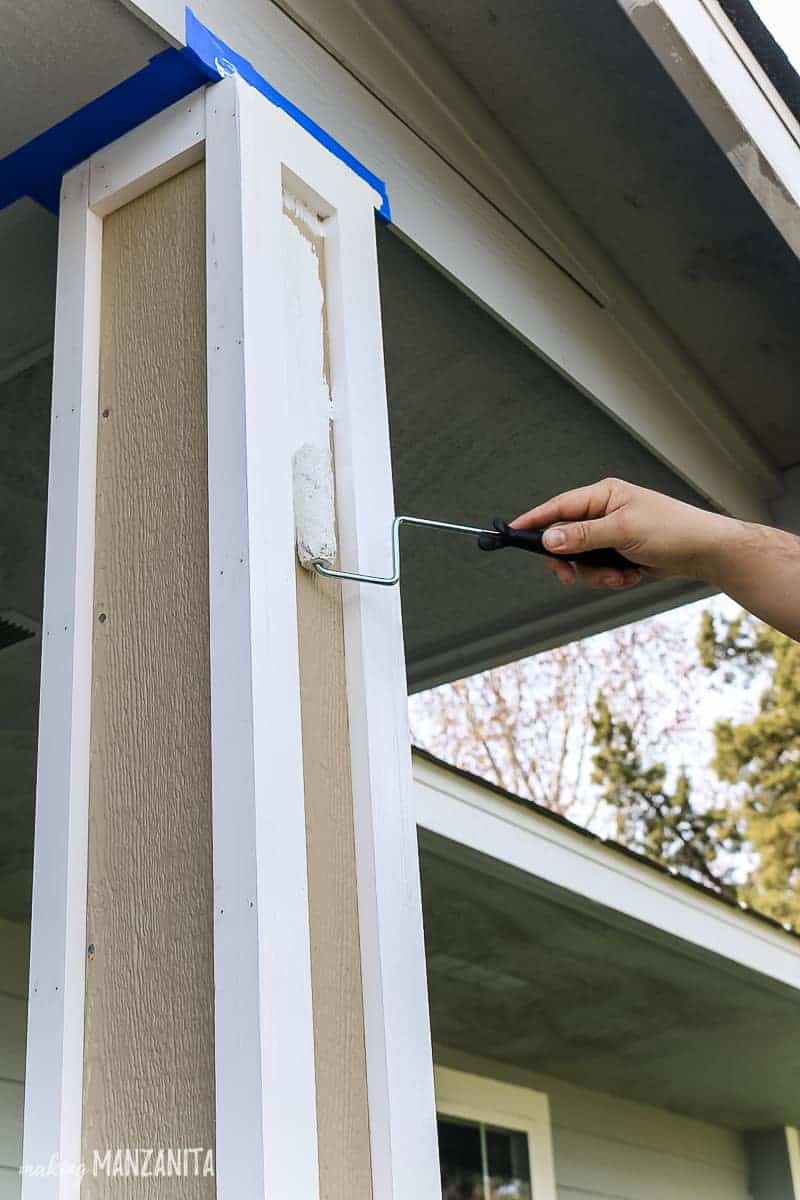 Man's hand rolling on white paint on to a new porch post with a 4 inch roller