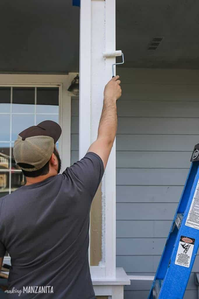 Man rolling white paint onto exterior porch posts with paint roller