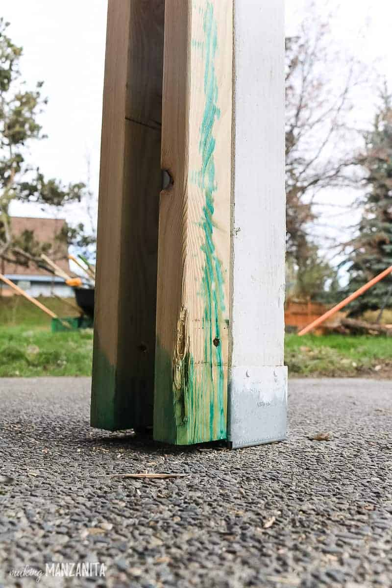 Copper green wood preservative sprayed on the bottom of 2x3s used for DIY porch posts to add curb appeal